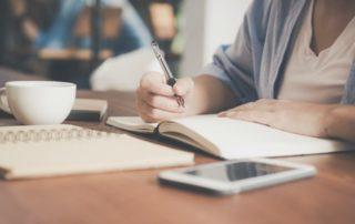 Vrouw zit aan tafel en schrijft in een notitieboek